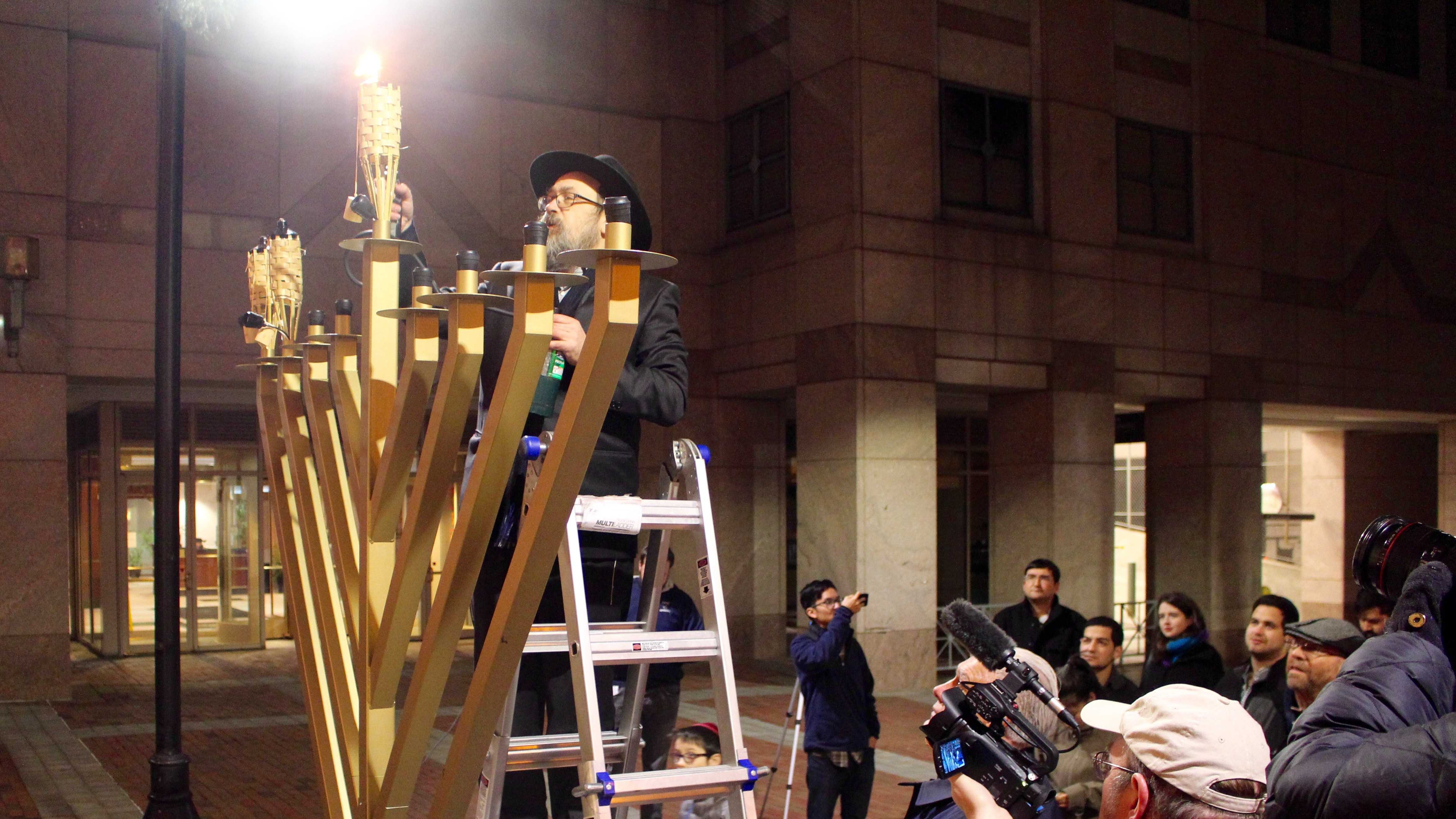 Rabbi Levi Krinsky lights the menorah.
