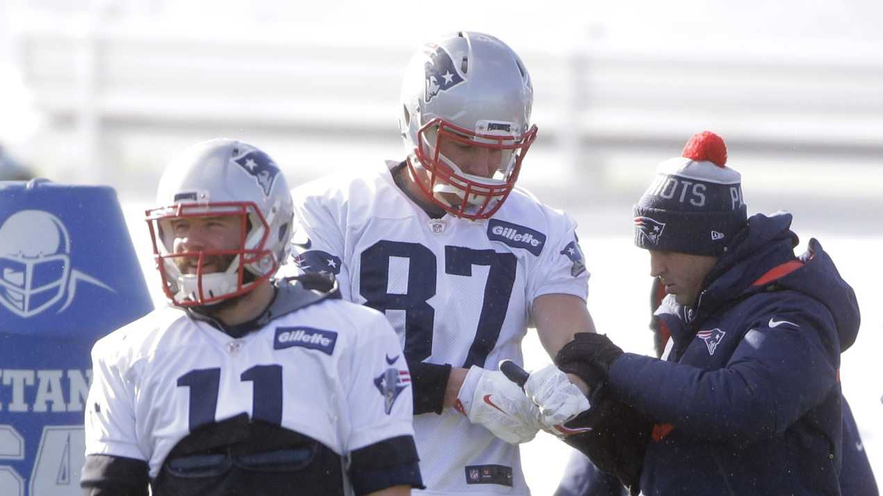 New England Patriots tight end Rob Gronkowski, center, has his arm tended to as wide receiver Julian Edelman, left, warms up on the field during an NFL football practice, Wednesday, Jan. 13, 2016, in Foxborough, Mass. The Patriots are to host the Kansas City Chiefs in an NFL divisional playoff game Jan. 16, 2016, in Foxborough.