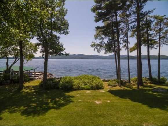 The home is surrounded by lake and mountain views and has access to a sandy beach with a covered dock.
