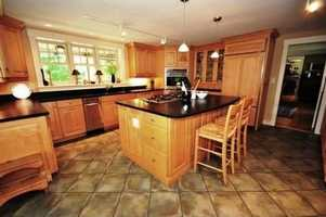 The large modern kitchen and dining area includes soapstone counter tops, plenty of storage space, and an island.