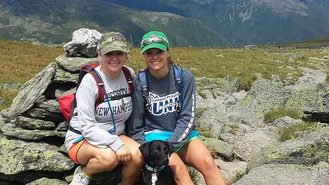 Melanie D'Andrea (left) and Cortney Stanley (right) with their dog Tripp while hiking up Mount Washington.