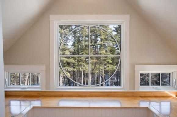 This custom window offers a view of scenic pine trees and a water backdrop.