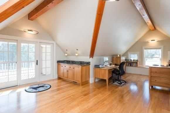 This office has red birch floors and an attached balcony.
