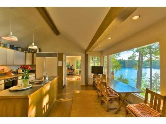The kitchen offers a large cooking and dining area, with a scenic view through a picture window.