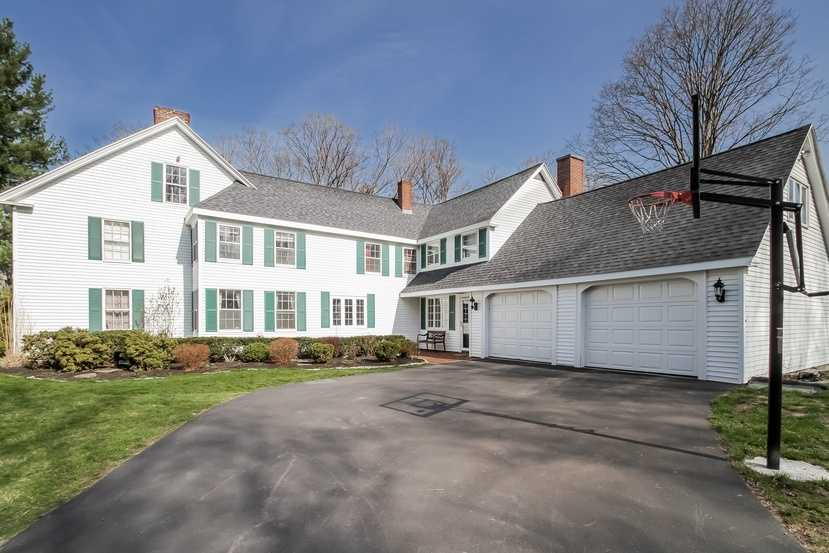 The home, which is located at 98 Sweet Hill Road, has a large driveway and a two-car garage.