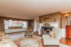 The spacious living room comes equipped with one of five fireplaces in the home.