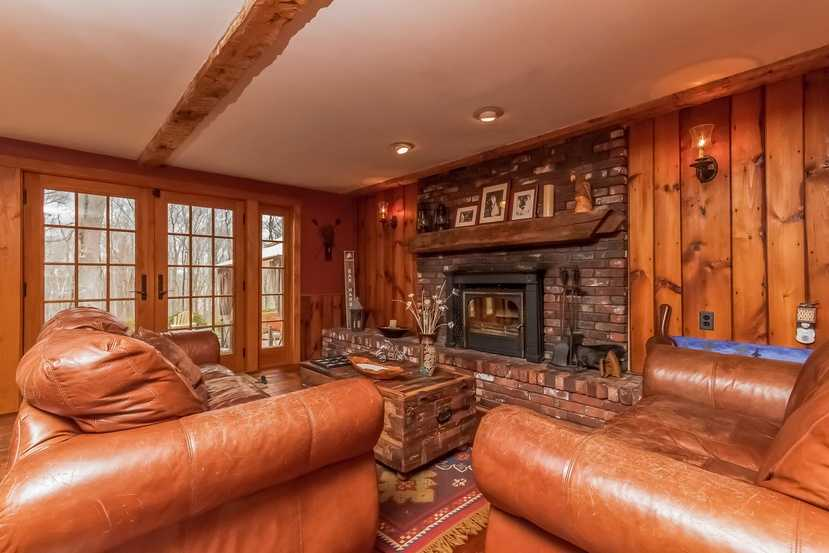 The family room has a fireplace, exposed beams and outdoor access.