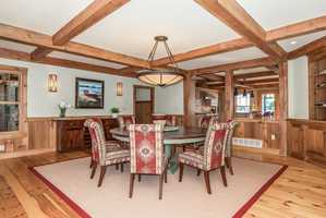 A view of the home's elegant dining room with hardwood floors and ceiling beams.