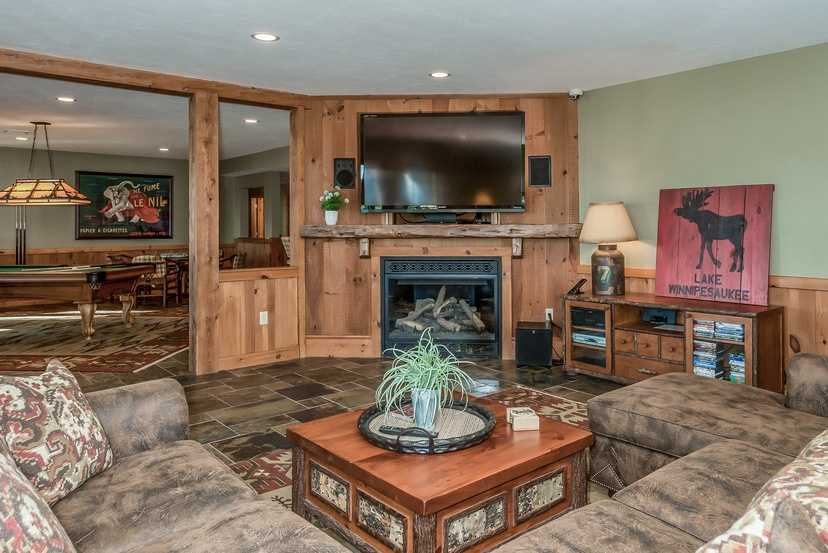 Additional seating in the game room offers a television and fireplace.