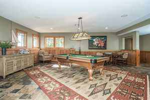 A large game room has a pool table and poker table.