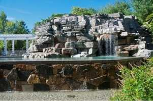 A waterfall flows through this scenic rock formation and into the pool.