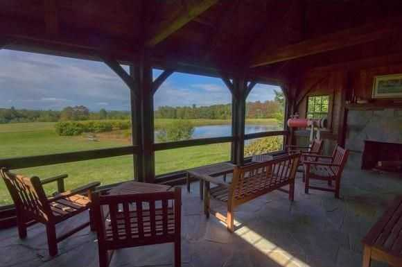 This screened porch has a stone fireplace.