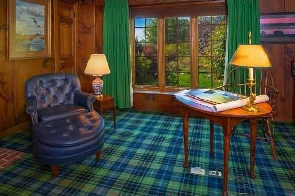 The great room has wonderful woodwork and carpeting.
