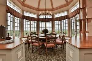 The formal dining area is surrounded by large windows.