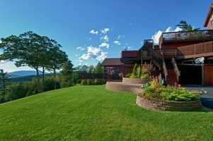 The home's expansive decks have an 8-person hot tub and can host 100 people.