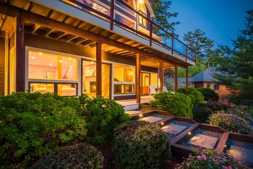 The home's landscape features beautiful lighting.