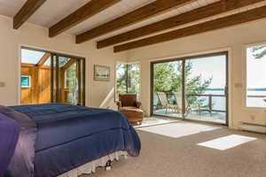This bedroom exits to a balcony that overlooks the lake and a hot tub area.