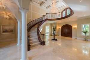 The home's 2-story foyer has lavish marble flooring and an elegant staircase.