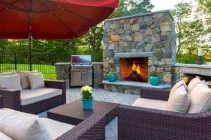 The patio as a large seating area, a grill and wooden fireplace.