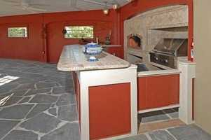 The home has an outdoor kitchen area that opens to a barn.