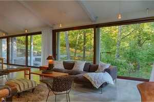 An open floor plan is accentuated by walls of windows opening to the natural landscape.