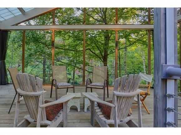 A glassed-in porch features natural wood work.