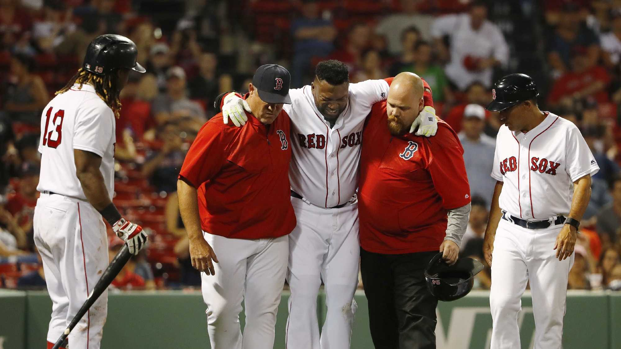 Boston Red Sox designated hitter David Ortiz is helped off the field by a trainer and manager John Farrell, left, as Hanley Ramirez, far left, looks on after fouling a ball off himself during the ninth inning of their 9-4 loss to the New York Yankees in a baseball game at Fenway Park in Boston on Wednesday, Aug. 10, 2016. Boston Red Sox's Bryce Brentz, far left, prepares to hit for Ortiz.