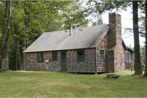 A pond-side cabin has a large field-stone fireplace.