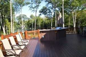 The back deck has plenty of seating, a grill and a bar.
