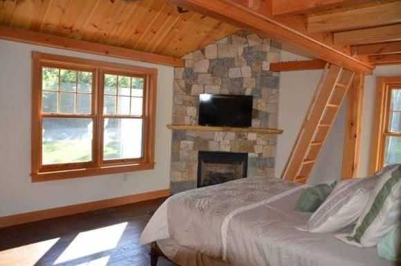 A look inside another bedroom with a fireplace and overhead loft.