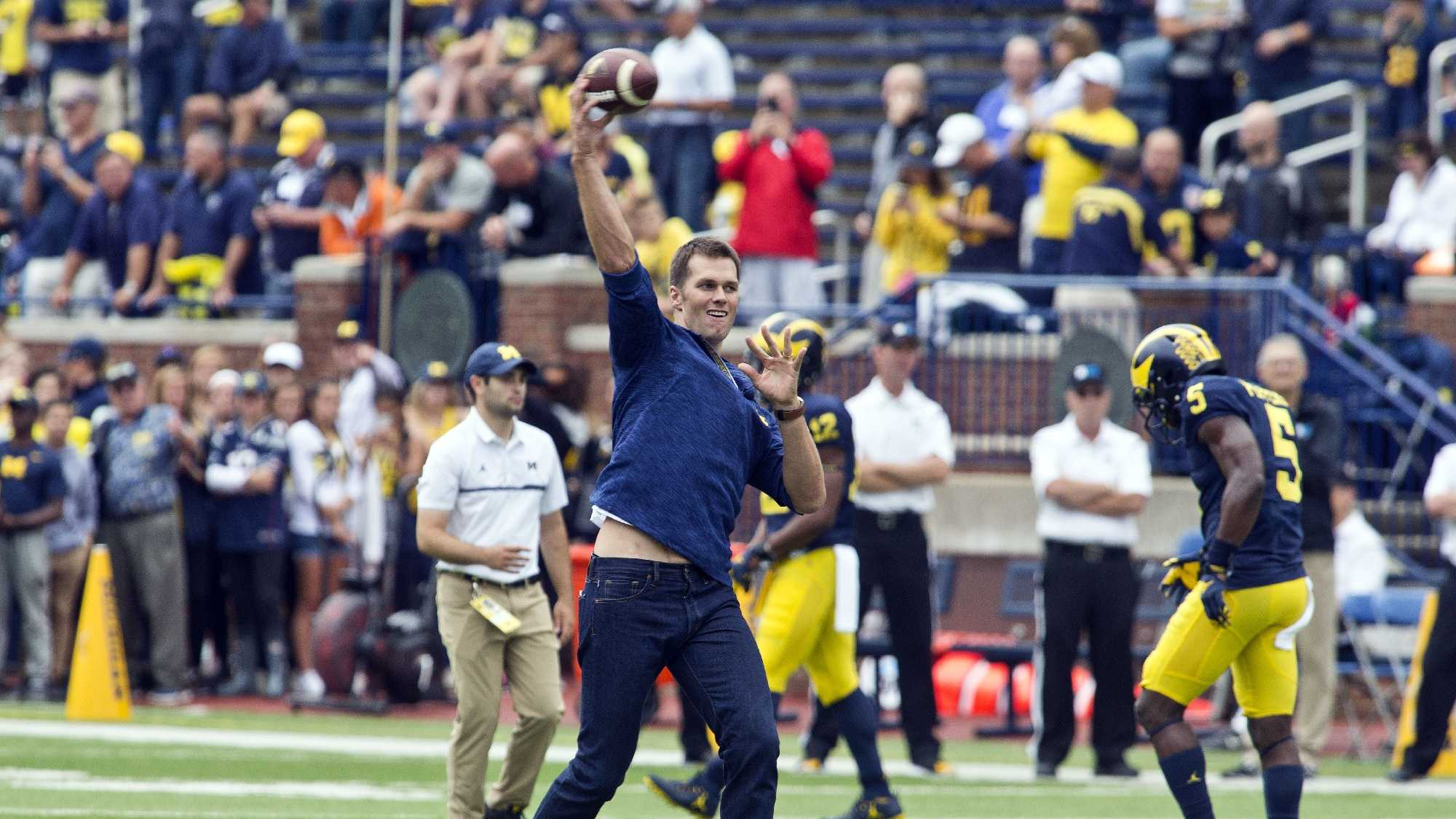 Former Michigan and currently suspended New England Patriots quarterback Tom Brady throws the football on the field before an NCAA college football game against Colorado at Michigan Stadium in Ann Arbor, Mich., Saturday, Sept. 17, 2016.