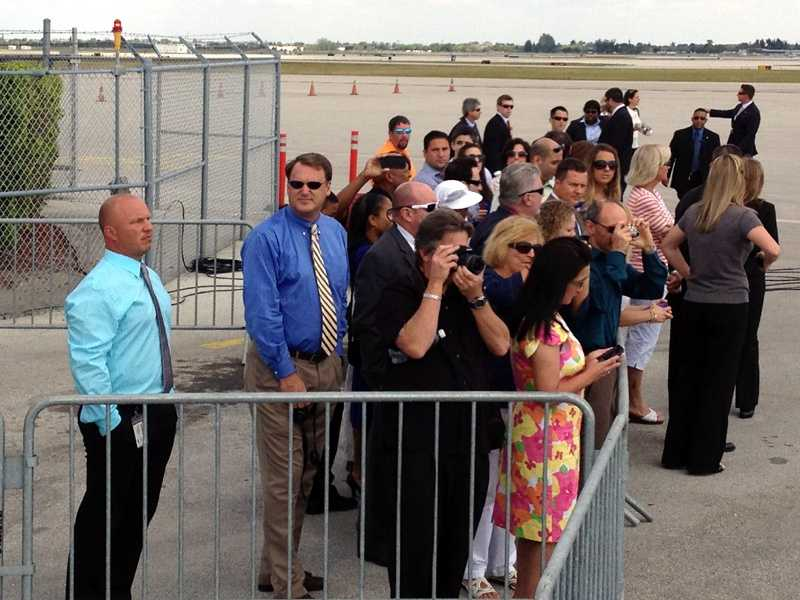 Curious onlookers await the arrival of Air Force One at Palm Beach International Airport.