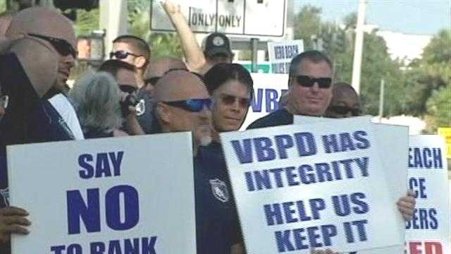 Dozens of Vero Beach police officers protest a plan that would eliminate positions and demote some top officials.