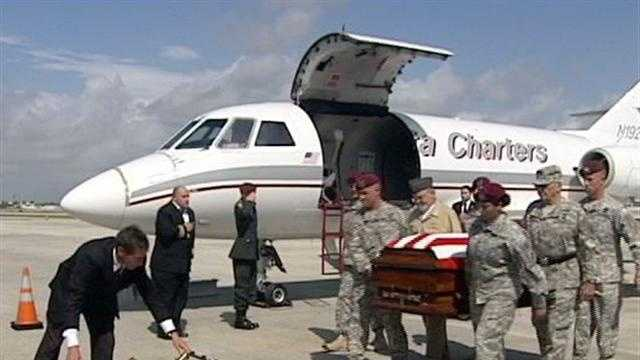 A casket carrying the body of Army soldier Michael Metcalf arrives at Palm Beach International Airport.