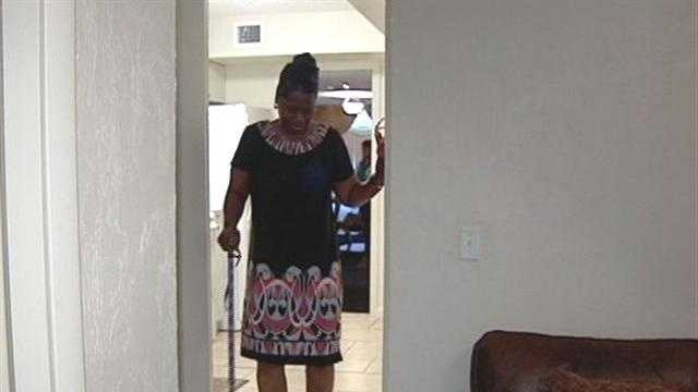 Rosa Wright walks with a cane through her new house, purchased courtesy of the Rev. Griffin Davis Sr.
