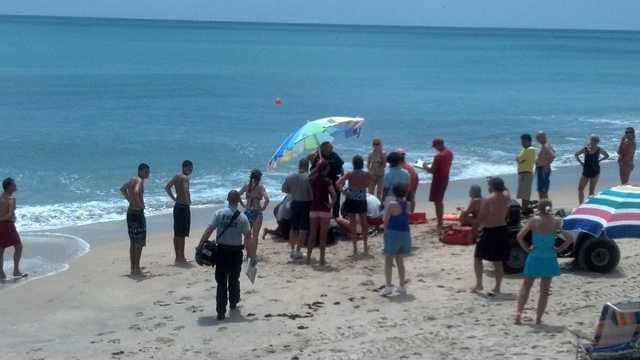 A woman is treated after being bitten by a shark. (Courtesy of Scott Weston)