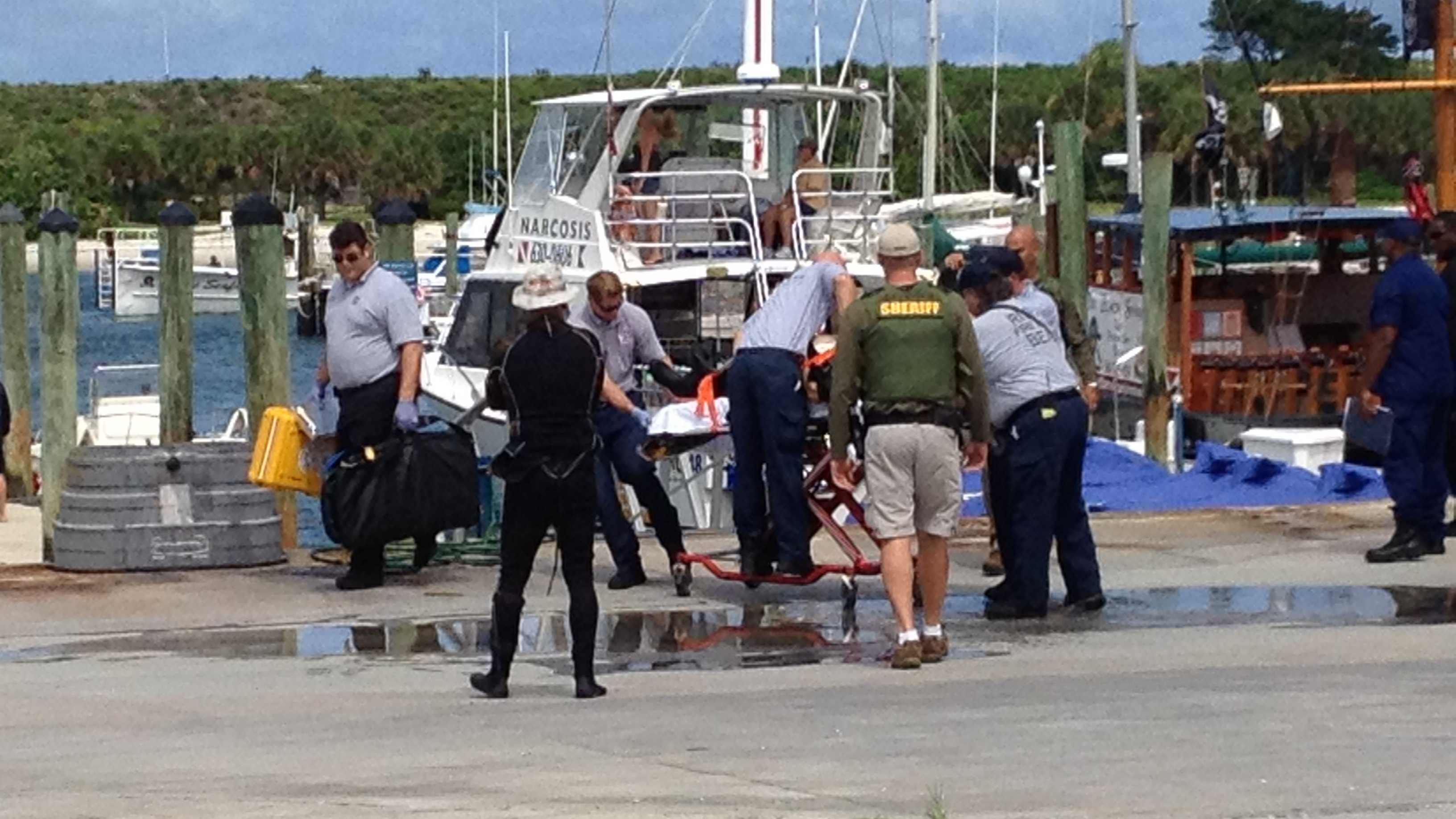 A scuba diver is placed on a stretcher after being brought to the Riviera Beach marina.