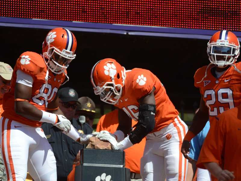"Arguably one of the most iconic scenes in all of college football, Clemson players rub ""Howard's Rock"" for good luck before they race down the hill and onto the field at Clemson Memorial Stadium before every home game. (Photo: Clemson SID)"
