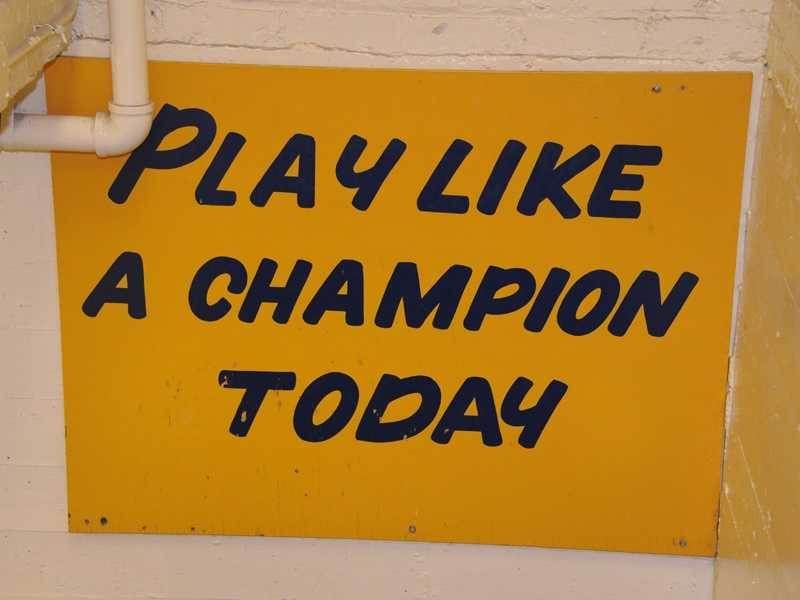 "The slogan ""Play Like a Champion Today"" is hand-painted in blue letters on a sign located in a stairwell between the home team locker room and the tunnel to the field of Notre Dame Stadium. It is a tradition for Notre Dame players to touch it on their way out of the locker room. (Photo: Notre Dame Athletics Media Relations)"
