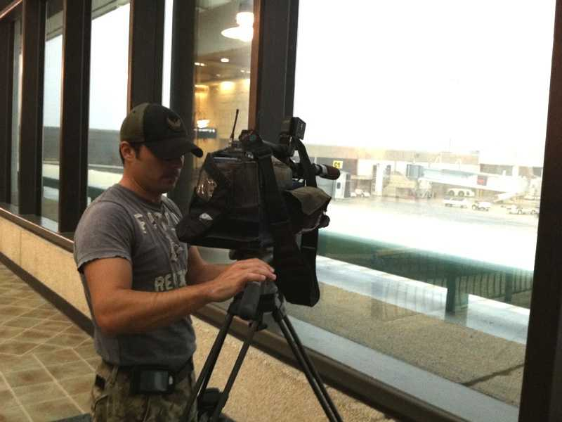 Erin Guy and her photographer, Kaan Pala, are talking with travelers at Palm Beach International Airport.