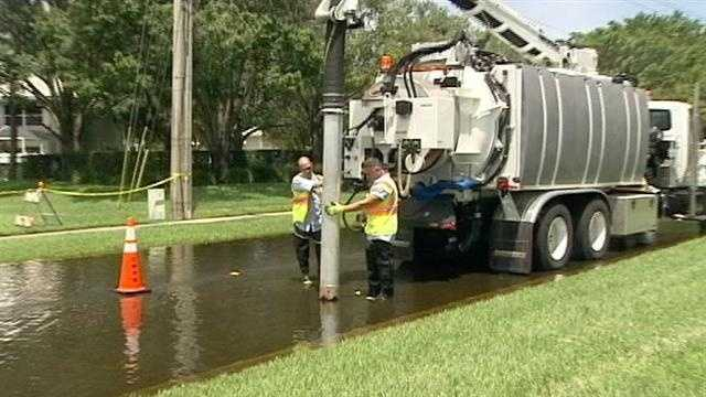 West Palm Beach employees use a truck to vacuum the floodwater and dispose of it in drains.