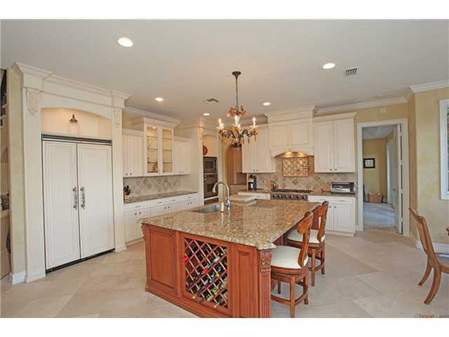 Spacious Mediterranean style kitchen, with wine cellar below the granite topped, over-sized island.