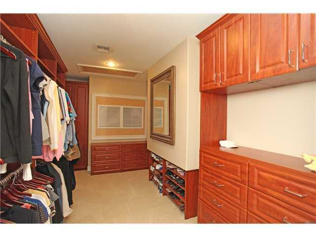 Custom wooden shelving in this walk in closet
