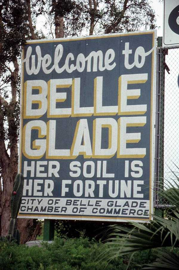 """Belle Glade (Palm Beach County): Belle Glade was originally known as the Hillsborough Canal Settlement. When the inhabitants requested their own post office, they were required to give the city a new name. A tourist traveling to the area said the town was the """"belle of the glades."""" That sounded good to the local residents, so with a minor change, it became the town's new name.  The photo is of the welcome sign to Belle Glade in 1988."""