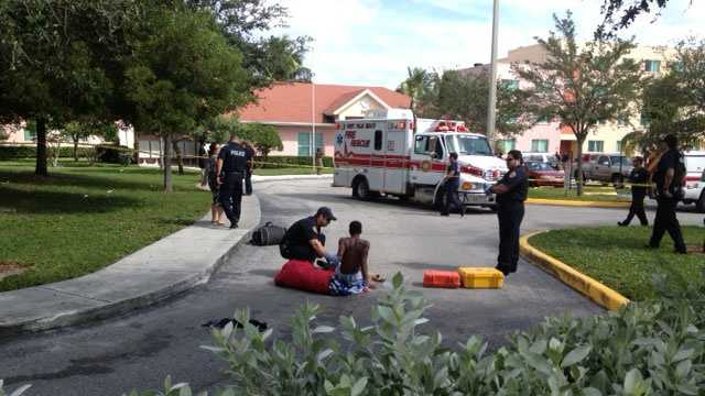 Paramedics treat a shooting victim at the Palm Grove Apartments.