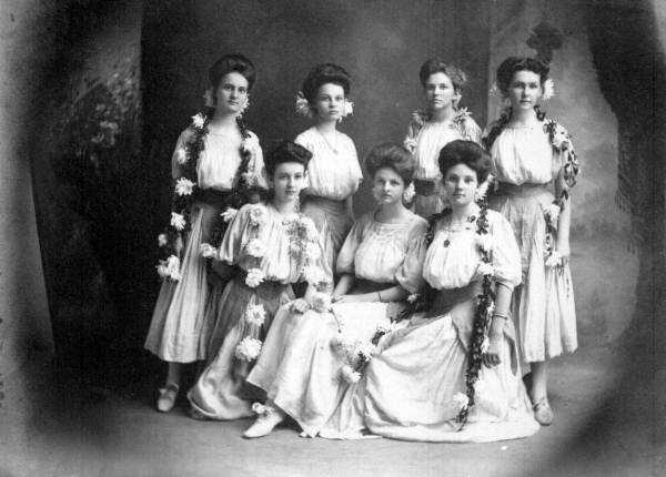 Seven young women pose wrapped in wreaths in the 1800s near Polk County.