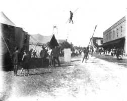 In 1890, a circus performer tight rope walks across Bay Street in Eustis.