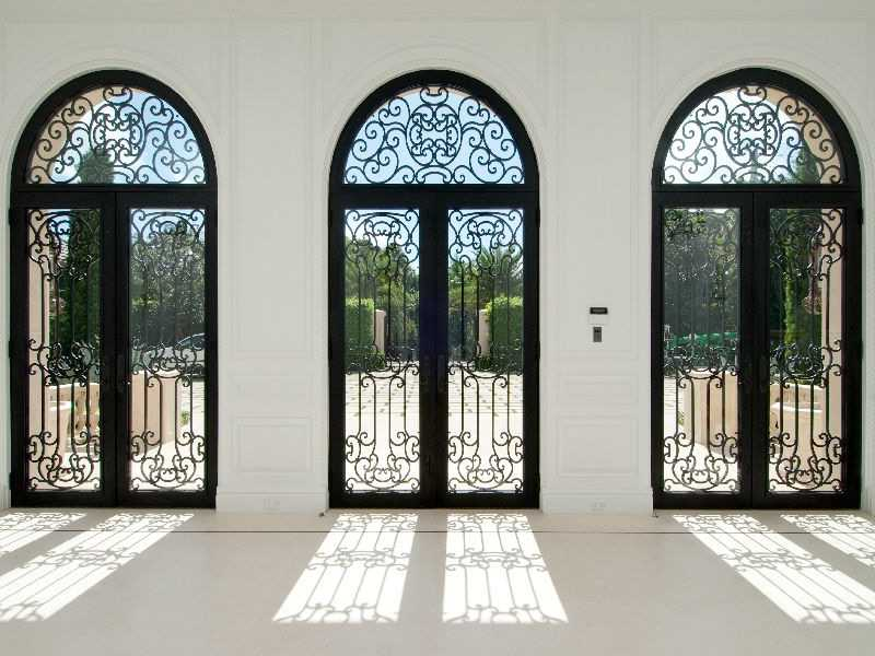 The grand iron gates create a formal entrance to the meticulously maintained landscape and residence.