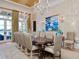 The dining room has an elegant appeal thanks to the tiered ceilings, chandeliers, and waterfront views.