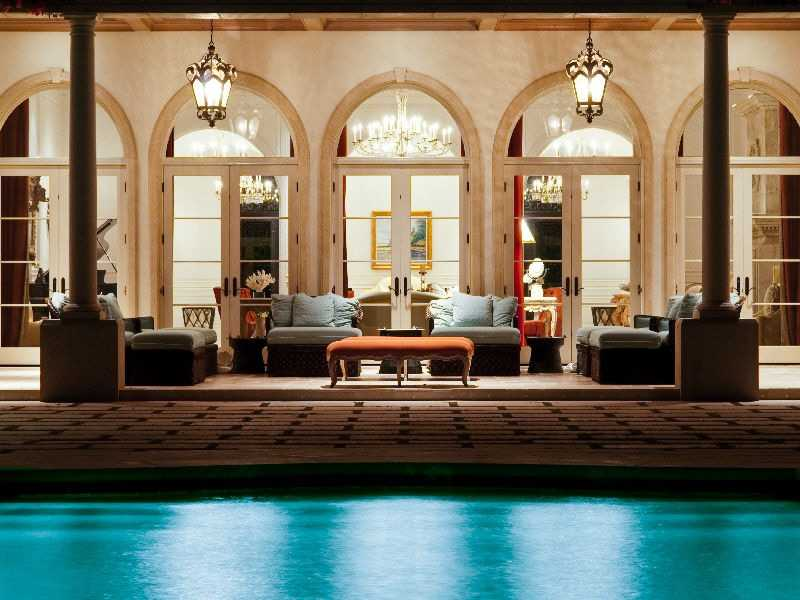 The outdoor patio is covered by the ceiling and overlooks a beautiful pool.